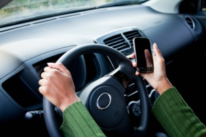 Female driver with mobile phone. Focus on hand holding phone